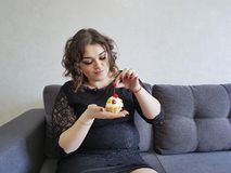 Beauty cute attractive full girl with cherry   pies on the sofa expression  pleasure breakfast Royalty Free Stock Photos