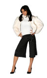 Beauty in fur. Attractive young woman in white fur coat with striped pants Royalty Free Stock Photo
