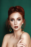 Beauty gentle glamour woman portrait red hair collected. On green background with brown ear-rings Stock Photography