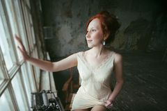 Beauty ginger woman at window, old house interior Stock Photo