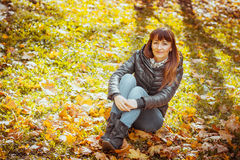 Beauty girl in autumn park. Sitting on a carpet of yellow leaves Stock Photo