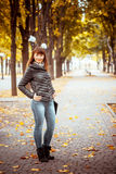 Beauty girl in autumn park. Sitting on a carpet of yellow leaves Stock Photography
