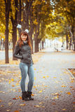 Beauty girl in autumn park. Sitting on a carpet of yellow leaves Royalty Free Stock Images