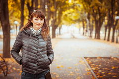 Beauty girl in autumn park. Sitting on a carpet of yellow leaves Royalty Free Stock Image