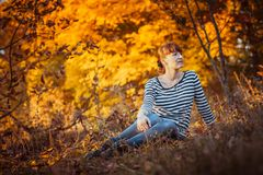 Beauty girl in autumn park. Sitting on a carpet of yellow leaves Stock Photos
