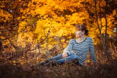 Beauty girl in autumn park. Sitting on a carpet of yellow leaves Royalty Free Stock Photography