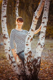 Beauty girl in autumn park. Standing near a tree Stock Photo