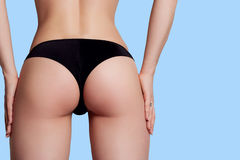 Beauty girl back pants string over blue background Stock Photo