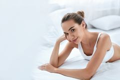 Beauty Girl With Beautiful Face And Skin Lying On White Bed royalty free stock images