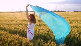 Beauty girl with the blue shawl. Running on the field stock footage