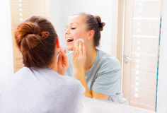 Beauty girl cleaning her face with cotton pads Stock Photo