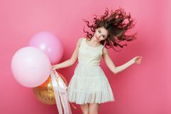 Beauty girl with colorful air balloons laughing over pink background. Beautiful Happy Young woman on birthday holiday party. Danci. Ng model having fun, playing Stock Photos