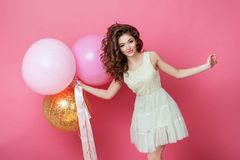 Beauty girl with colorful air balloons laughing over pink background. Beautiful Happy Young woman on birthday holiday party. Fashi. On model having fun, playing Stock Image