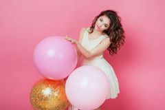 Beauty girl with colorful air balloons laughing over pink background. Beautiful Happy Young woman on birthday holiday party. Fashi. On model having fun, playing Stock Photo