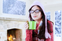 Beauty girl drinking hot beverage. Young asian girl wearing sweater and enjoy hot drink at home with winter background Royalty Free Stock Photo