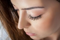 Beauty girl with extended silk eyelashes and eyes closed in a beauty studio, close up royalty free stock photo