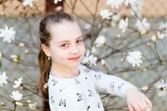 Beauty girl on floral blossom in spring. Beauty kid with fresh look and long hair.  royalty free stock photo