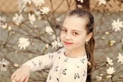 Beauty girl on floral blossom in spring. Beauty kid with fresh look and long hair.  royalty free stock photography