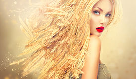 Beauty girl with gold long wheat ears hair. Beauty fashion model girl with gold long wheat ears hair Royalty Free Stock Image