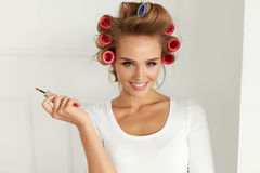 Beauty. Girl With Hair Curlers Curling Hair, Putting Lip Gloss stock photography