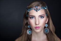 Beauty girl jewelry. Beauty with large oriental ornaments jewelry silver circle earrings, tiara with blue black stones. Long light hair, beige skin, professional Royalty Free Stock Photo