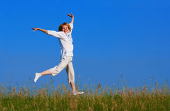 Beauty girl jumping in field stock photos