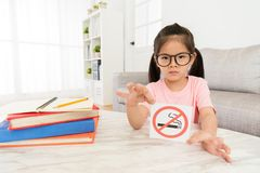 Beauty girl kid showing no smoking sign to camera. Beauty elegant girl kid showing no smoking sign to camera when she doing school studying homework in living Royalty Free Stock Photos