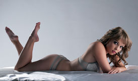 Beauty girl lay and smile in bed, sexy lingerie Royalty Free Stock Photo