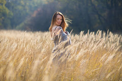 Beauty girl with long red blowing hair outdoors. Royalty Free Stock Photography