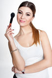 Beauty Girl make up artist with Makeup Brush. Bright Holiday Make-up for Brunette Woman with Brown Eyes.  Beautiful Face. Makeover Stock Image