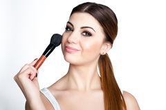 Beauty Girl make up artist with Makeup Brush. Bright Holiday Make-up for Brunette Woman with Brown Eyes.  Beautiful Face. Makeover Stock Photo
