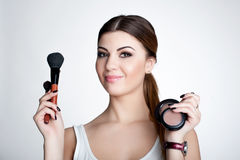 Beauty Girl make up artist with Makeup Brush. Bright Holiday Make-up for Brunette Woman with Brown Eyes.  Beautiful Face. Makeover Stock Photography