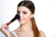 Beauty Girl make up artist with Makeup Brush. Bright Holiday Make-up for Brunette Woman with Brown Eyes.  Beautiful Face. Makeover Royalty Free Stock Image