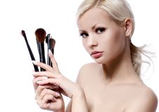 Beauty girl with makeup brushes isolated on white. beautiful blonde Royalty Free Stock Photos