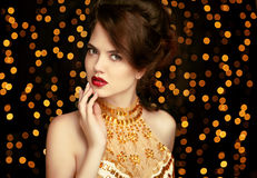 Beauty girl makeup. Fashion jewelry. Elegant lady in golden dress. On dark with Christmas party lights background. Vogue style Royalty Free Stock Photos