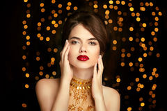 Beauty girl makeup. Fashion jewelry. Elegant lady in golden dress. On dark with Christmas party lights background. Vogue style Stock Images