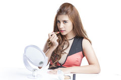 Beauty girl makeup routine. Young woman applying lipstick in the mirror Royalty Free Stock Photography