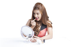 Beauty girl makeup routine. Young woman applying lipstick in the mirror Royalty Free Stock Image