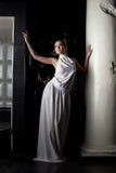 Beauty girl near column in fashion dress Stock Photos