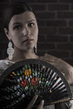 Beauty girl no make up, with hand fan and earrings Stock Photos
