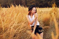 Beauty Girl Outdoors enjoying nature. Pretty Teenage Model in hat running on the Spring Field, Sun Light. Romantic. Young blonde girl in a wheat field. Woman in stock photography