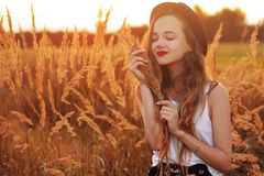 Beauty Girl Outdoors enjoying nature. Pretty Teenage Model in hat running on the Spring Field, Sun Light. Romantic young blonde g royalty free stock photography