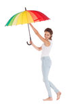 Beauty girl playing with multy color umbrella. Isolated on white background Stock Images