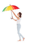 Beauty girl playing with multy color umbrella. Isolated on white background Stock Image