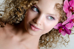 Beauty girl portrait with purple orchid Royalty Free Stock Photography