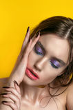 Beauty Girl Portrait with Vivid Makeup. Fashion Woman portrait close up on yellow background. Bright Colors. Manicure Make up. Smo Stock Photo