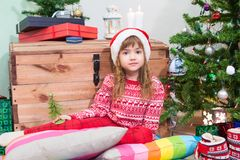 Beauty Caucasian girl in red Christmas clothes sitting near green tree and looking at camera. Beauty girl in red Christmas clothes sitting near green tree and Stock Images