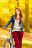 Beauty girl relaxing in autumn park with bicycle, outdoor Royalty Free Stock Photo