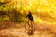 Beauty girl relaxing in autumn park with bicycle, outdoor Stock Photography