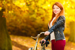 Beauty girl relaxing in autumn park with bicycle, outdoor Stock Photo